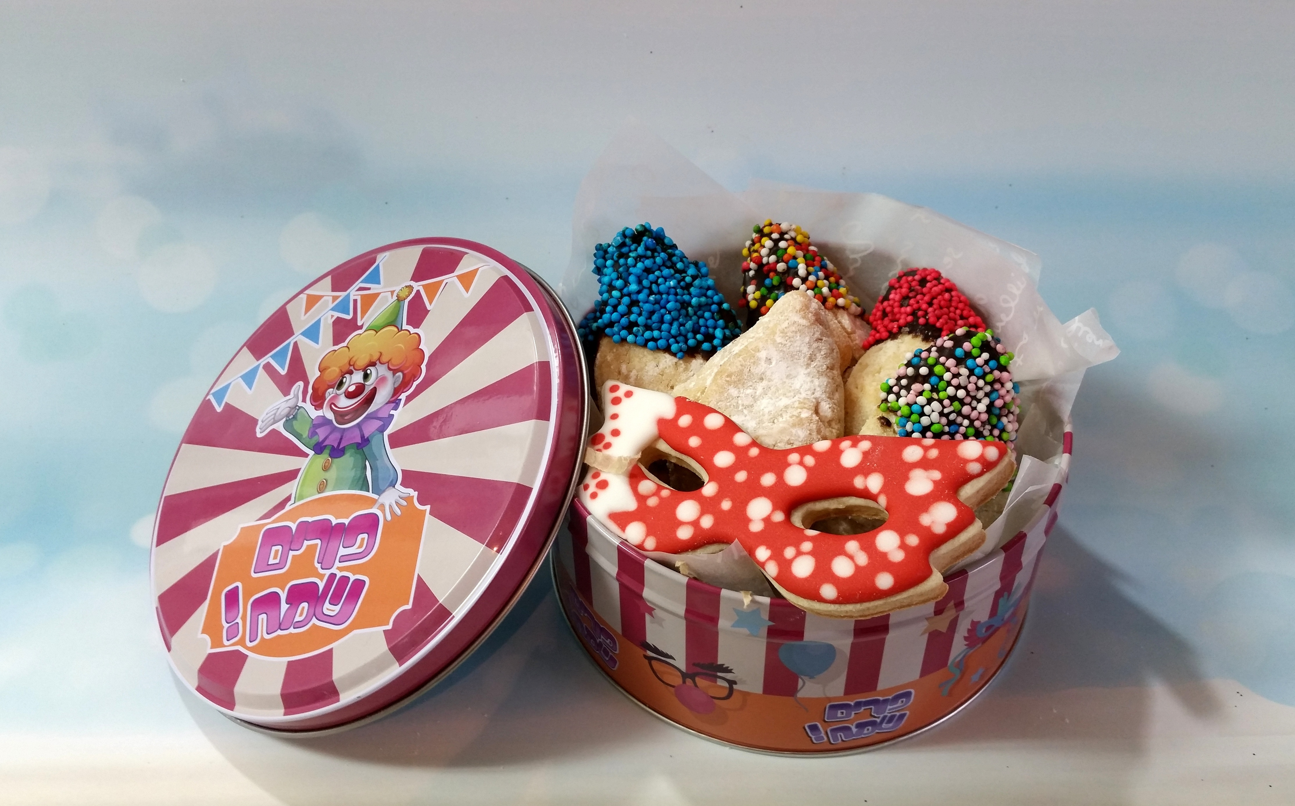 tin box with humantaschen dippted in chocolate and candy with 1 decorated cookie